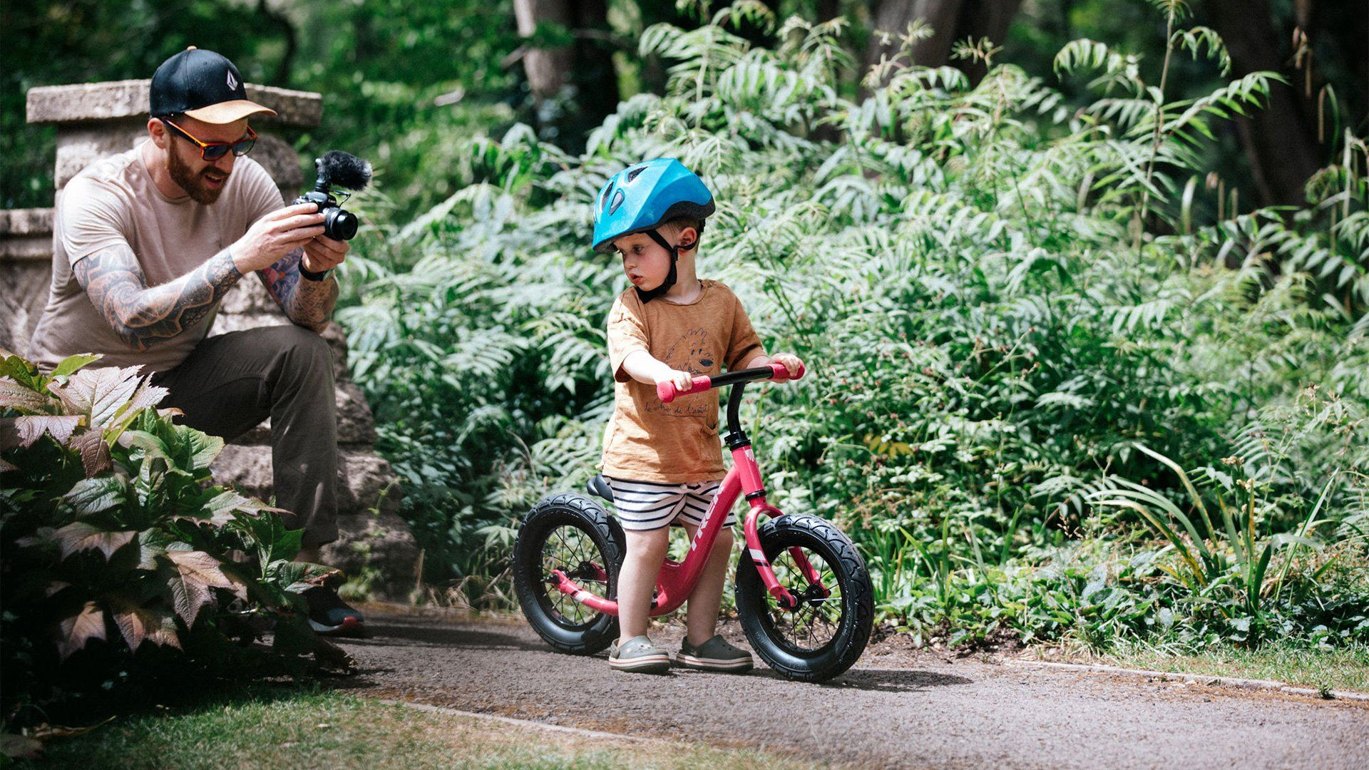 Stef Michalak crouching on a path with a Canon EOS M50 to film his son's first ride on a balance bike.